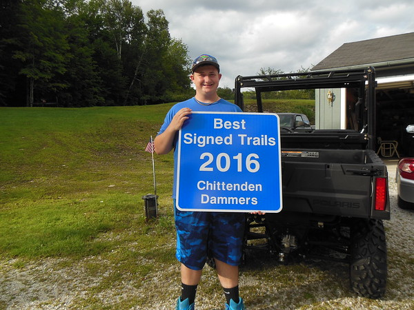 Collin Racine posing with the new sign awarded to the Chittenden Dammers at the VAST annual meeting.